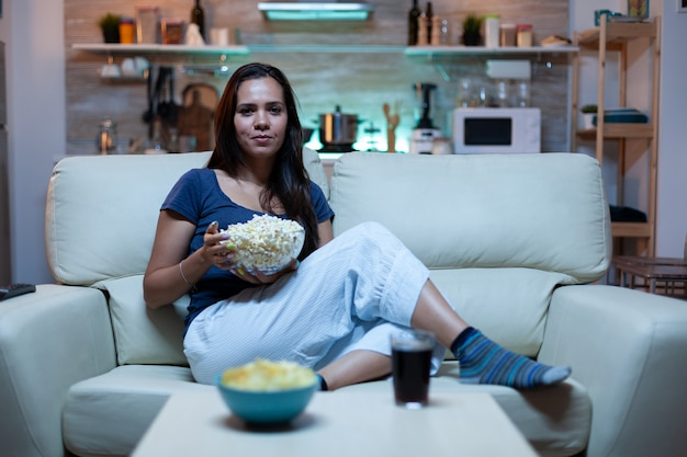 Young lady in pijamas watching tv in living room sitting on sofa
