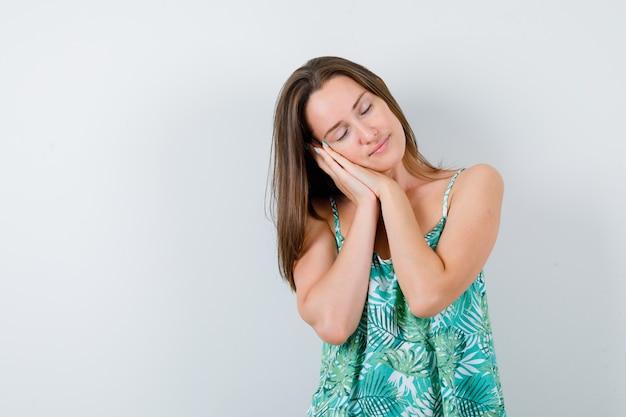 Giovane donna che si fa cuscino sulle mani in camicetta e sembra assonnata. vista frontale.