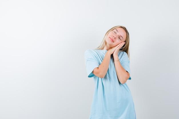 Giovane donna che si fa il cuscino sulle mani in maglietta e sembra assonnata isolata