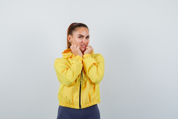 Young lady pillowing face on her hands in yellow jacket and looking peaceful. front view.