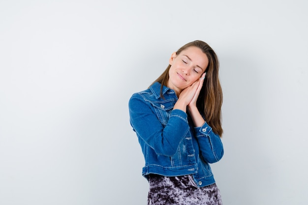 블라우스, 데님 재킷, 졸려 보이는 전면 보기에 그녀의 손에 얼굴을 베개 젊은 여자.