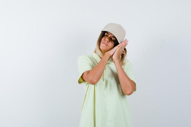 Tシャツ、キャップ、眠そうな顔を手に枕で飾る若い女性。正面図。