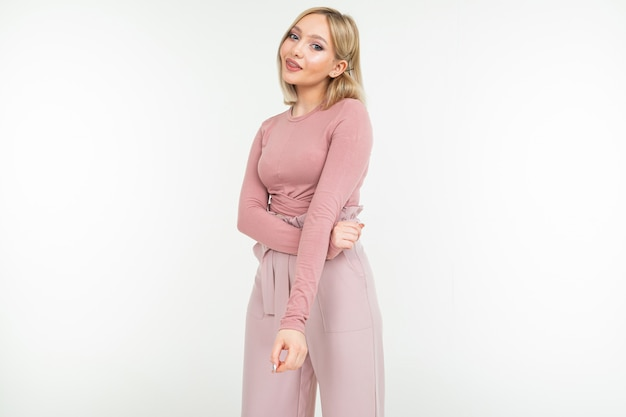Young lady in a pink blouse and trousers flirts on a white studio background