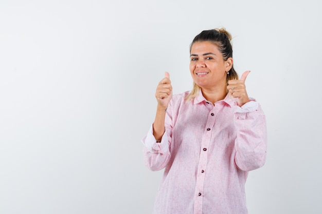 Young lady in pink shirt showing double thumbs up and looking merry