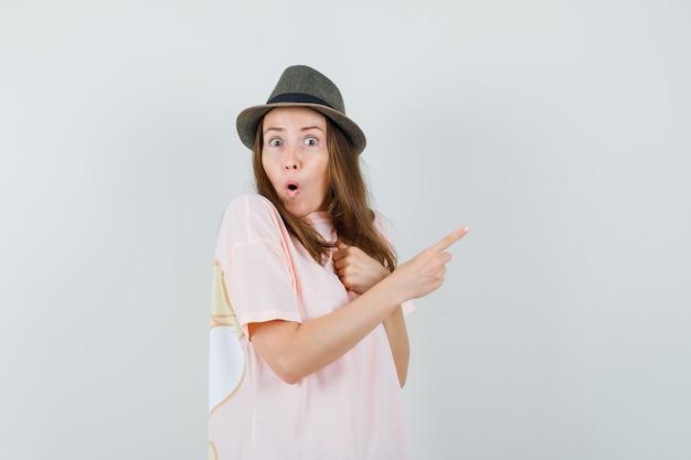 Giovane donna in cappello di maglietta rosa che punta verso il lato destro e che sembra meravigliata