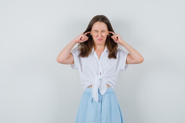 Giovane donna che collega le orecchie con le dita in camicetta, gonna e sembra irritata