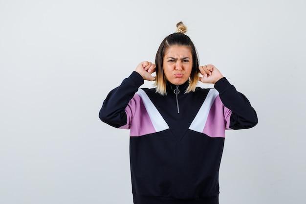 パーカーのセーターに指で耳を差し込んで悲しそうに見える若い女性