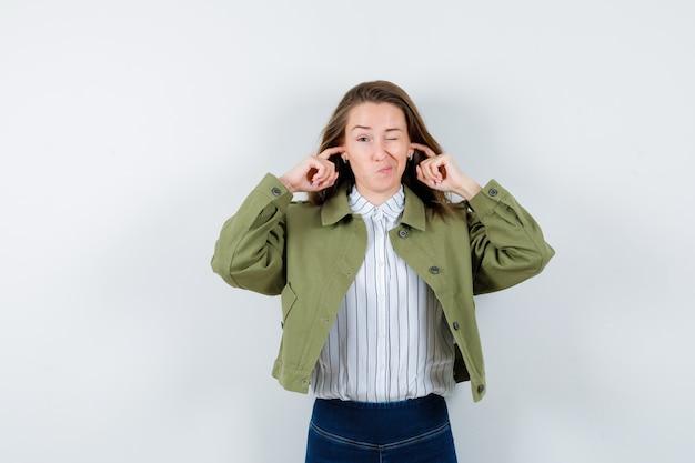 シャツ、ジャケットに指で耳を塞いで躊躇しているお嬢様、正面図。