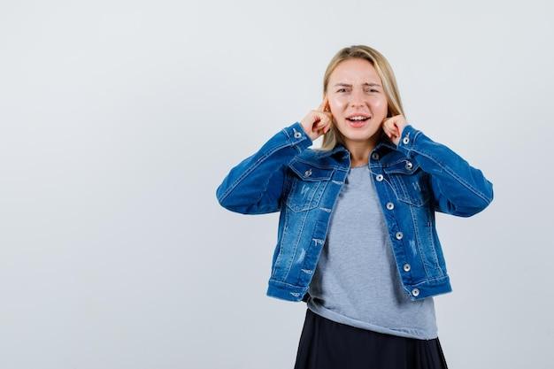 Tシャツ、デニムジャケット、スカートに指で耳を差し込んで混乱している若い女性