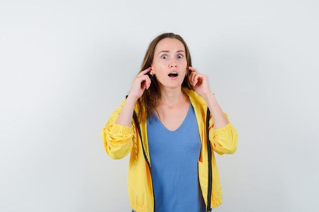 若い女性がtシャツ、ジャケットに指で耳を差し込んで、驚いた正面図を見てください。