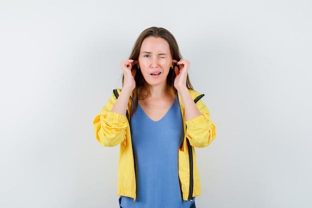 Tシャツ、ジャケットに指で耳を差し込んで好奇心旺盛な若い女性。正面図。