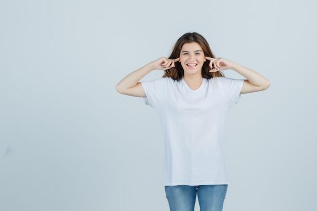 젊은 아가씨 t- 셔츠, 청바지에 손가락으로 귀를 연결 하 고 즐거운, 전면보기를 찾고.