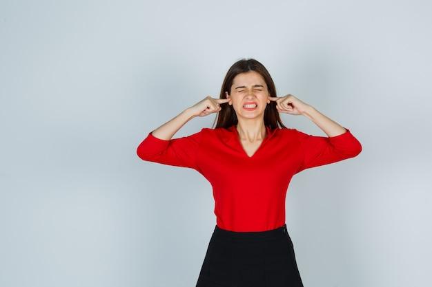 Giovane donna tappando le orecchie con le dita in camicetta rossa, gonna e guardando infastidito