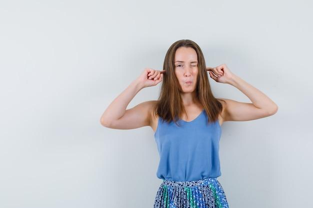 Giovane donna che collega le orecchie con le dita in canottiera, gonna e sembra curiosa