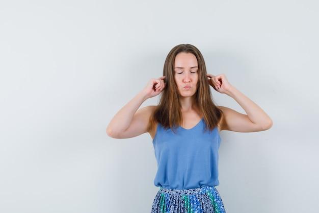 Giovane donna tappando le orecchie con le dita in canottiera, gonna e guardando rilassato
