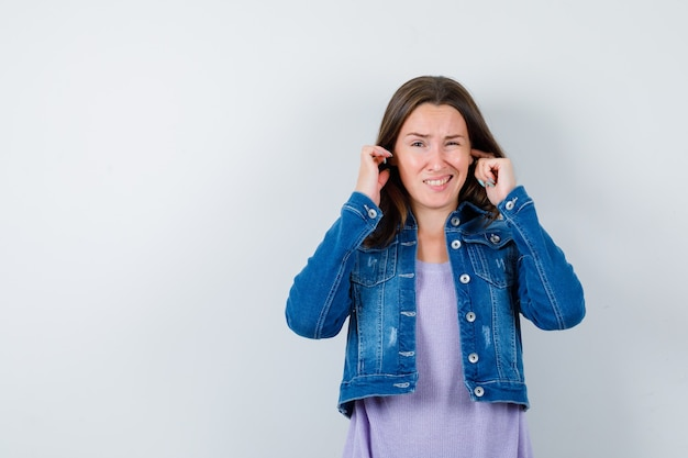 Young lady plugging ears with fingers in t-shirt, jacket and looking bored. front view.
