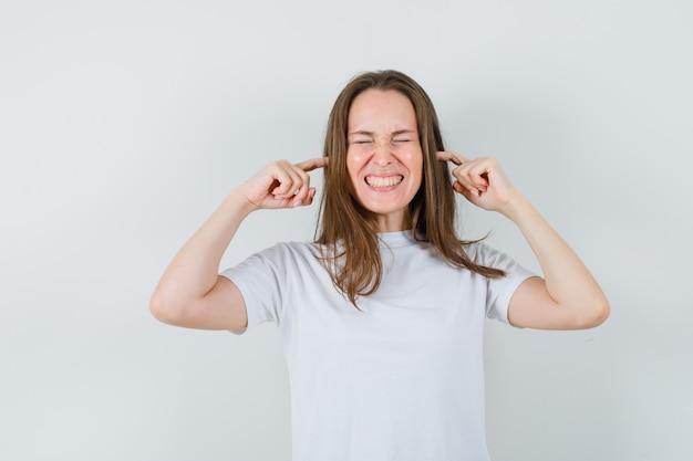 Giovane donna che collega le orecchie con le dita in maglietta bianca e sembra infastidita