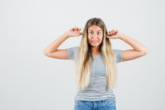 Giovane donna tappando le orecchie in t-shirt e guardando annoiato, vista frontale.