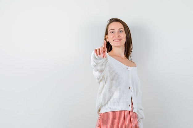 Young lady pointing aside in cardigan and skirt looking blissful isolated