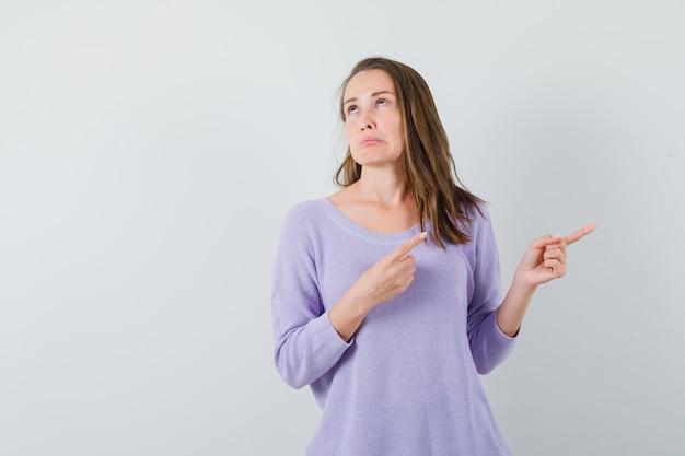 Молодая дама указывает в сторону в повседневной рубашке и выглядит высокомерно