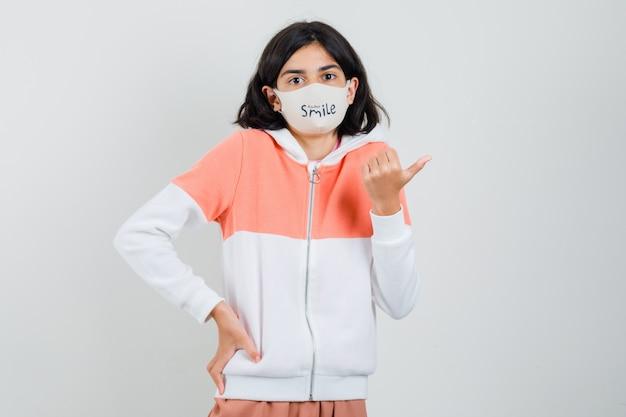 パーカー、フェイスマスクで脇を指して、安心して見える若い女性