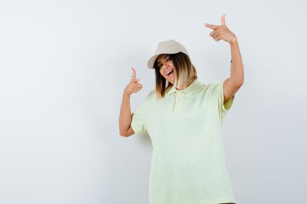 옆으로 t- 셔츠, 모자를 가리키고 행복을 찾고 젊은 아가씨. 전면보기.
