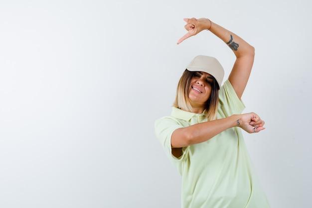 T- 셔츠, 모자에 옆으로 가리키고 즐거운 찾고 젊은 아가씨. 전면보기.