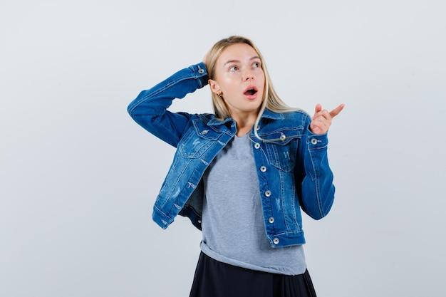 옆으로 티셔츠, 데님 재킷, 스커트를 가리키고 놀란 젊은 아가씨