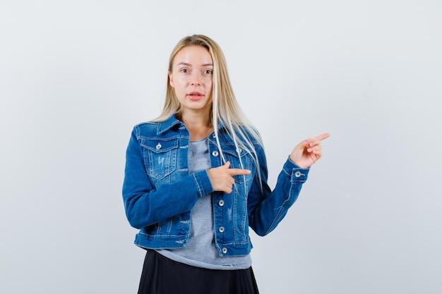 옆으로 t- 셔츠, 데님 재킷, 치마를 가리키고 매력적인 찾고 젊은 아가씨.