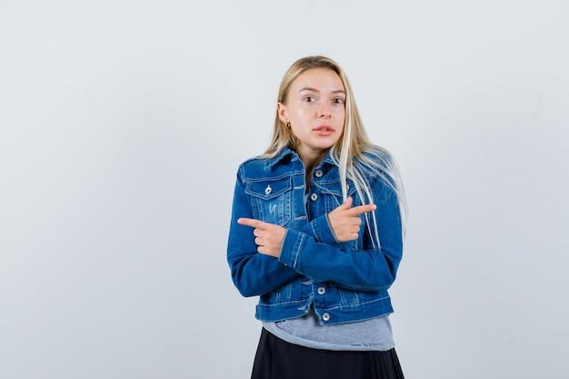 옆으로 티셔츠, 데님 재킷, 치마를 가리키고 자신감을 찾고 젊은 아가씨