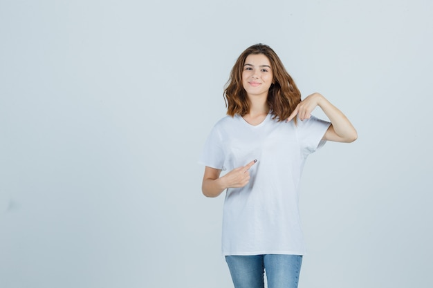 Tシャツ、ジーンズで脇を向いて陽気に見える若い女性。正面図。