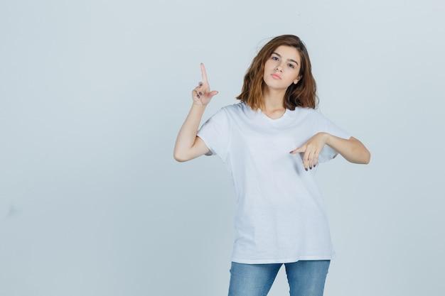Tシャツ、ジーンズで脇を指して、自信を持って、正面図を探している若い女性。