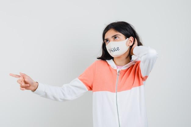 Молодая леди указывая в сторону, держа руку на шее в толстовке с капюшоном, маске для лица и выглядя грустно.