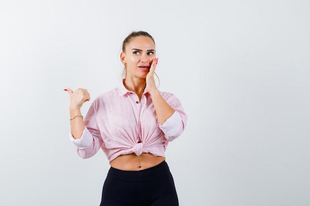 Giovane donna che indica da parte con il pollice, tenendo la mano sulla guancia in camicia, pantaloni e guardando curioso. vista frontale.