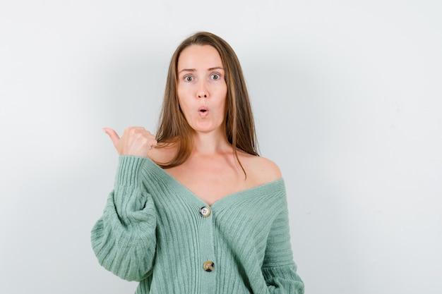 ウールのカーディガンで親指で脇を向いて驚いた若い女性。正面図。