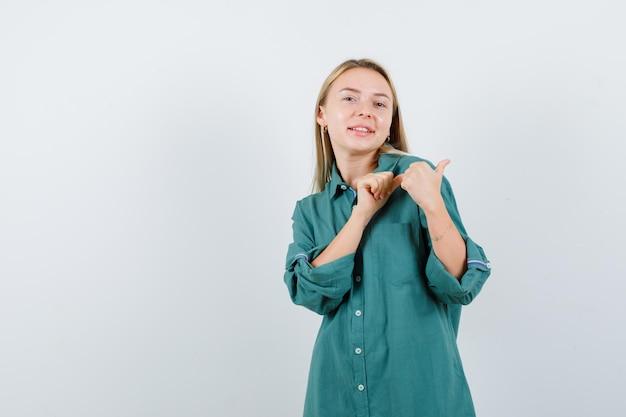 Giovane donna che indica da parte con i pollici in camicia verde e sembra allegra