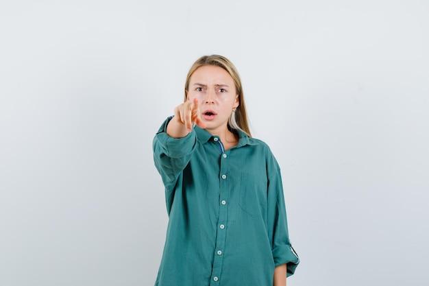 緑のシャツを着てカメラを指して真剣に見える若い女性