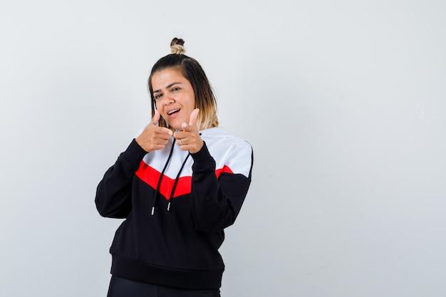 パーカーのセーターでカメラを指して、陽気に見える若い女性。