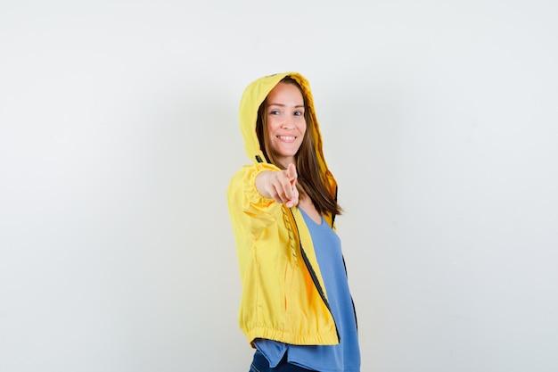Tシャツ、ジャケット、自信を持って、正面図でカメラを指している若い女性。
