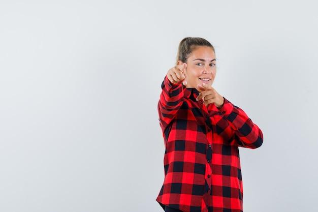 チェックのシャツを着て正面を指して自信を持って見える若い女性