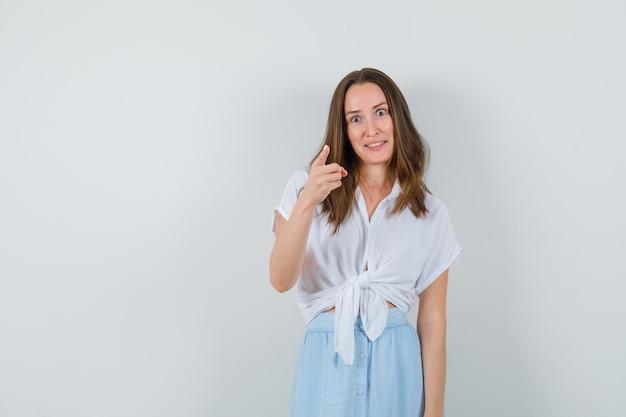 白いブラウス、青いスカートで正面を指して集中して見える若い女性