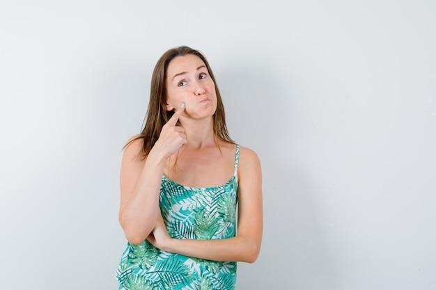 ふくらんでいる頬を指さし、目をそらし、困惑している若い女性。正面図。