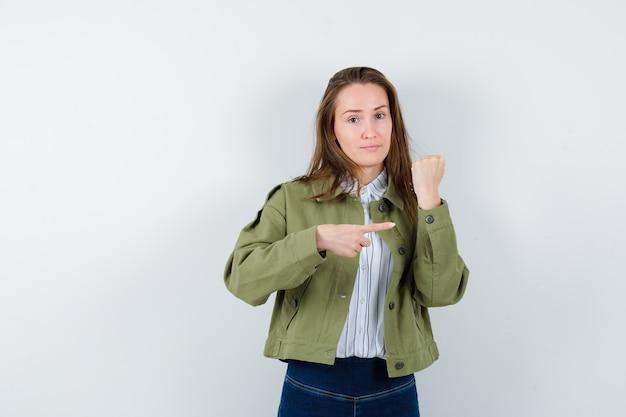 Девушка в рубашке и пиджаке, указывая на рукав и выглядя очаровательно. передний план.