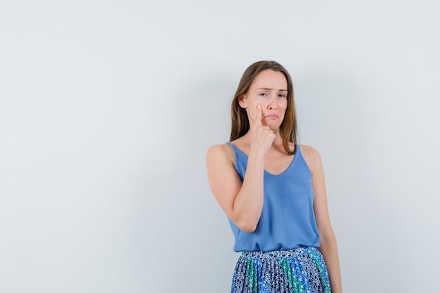 ブラウス、スカートで彼女の涙を指して、動揺している若い女性、正面図。テキスト用のスペース