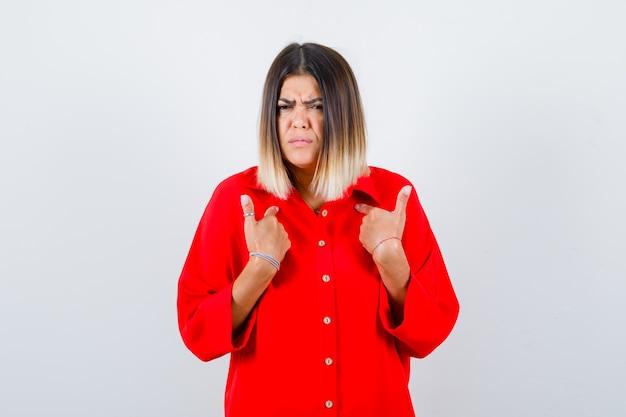 빨간 특대형 셔츠에 질문을 하고 진지한 정면을 바라보며 자신을 가리키는 젊은 여성.