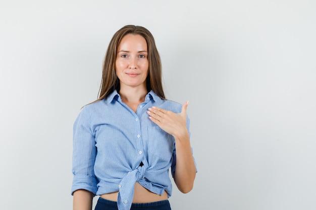 Молодая дама указывает на себя в синей рубашке, штанах и выглядит оптимистично