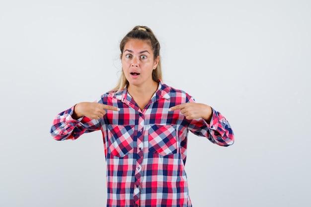 チェックのシャツを着て自分を指差して困惑している若い女性。正面図。