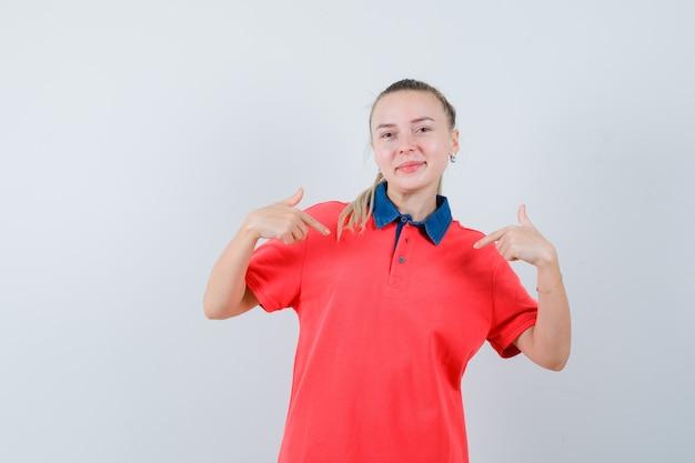 Молодая дама указывает на себя в футболке и гордится