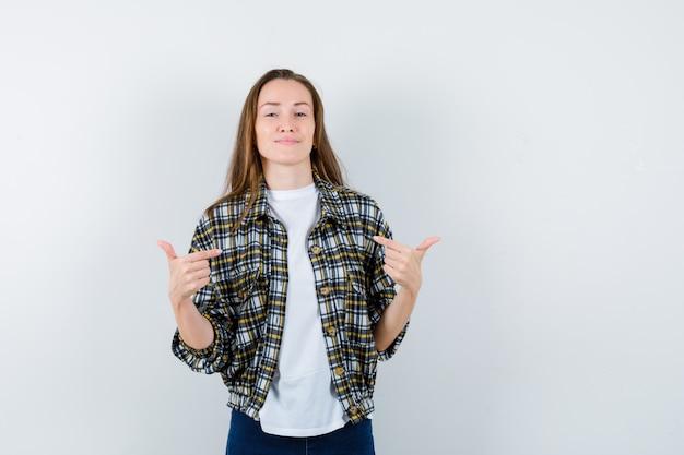 T- 셔츠, 재킷, 청바지에 자신을 가리키고 자랑스럽게 보이는 젊은 아가씨. 전면보기.