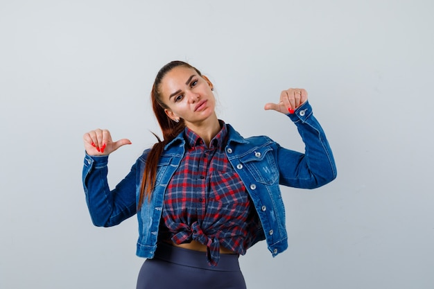 市松模様のシャツ、デニムジャケットを親指で指さし、自信を持って見える若い女性。正面図。